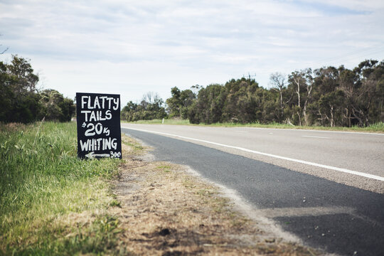 Black and white roadside sign advertising flathead tails horizontal