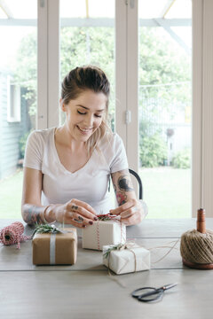 Young woman wrapping gifts in a light bright interior