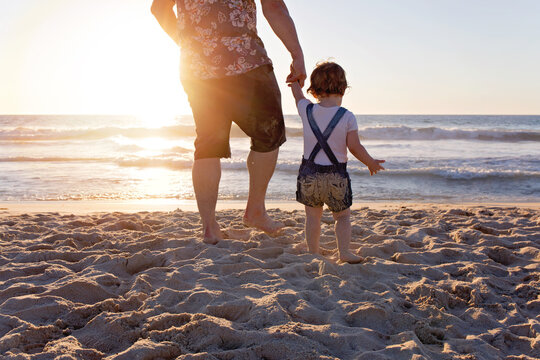 Father Holding His Daughter's Hand Walking Towards The Ocean At Sunset