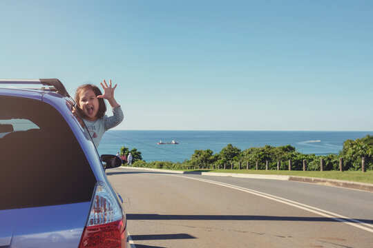 Little girl in the car on roadside with ocean background