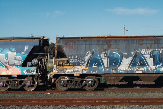Tagged and graffitied goods train carriages travelling on tracks