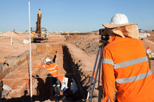 Industrial workers surveying a large building site