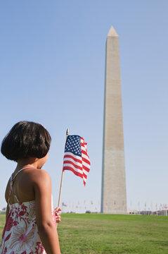 USA, Washington DC, girl (10-11) with US flag in front of Washington Monument
