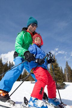 USA, Colorado, Telluride, Father with son (8-9) skiing together