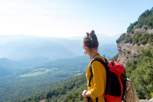Rear view of a young woman standing on high mountain looking at view