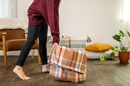 Woman Grabs Basket With Blanket and Pillow