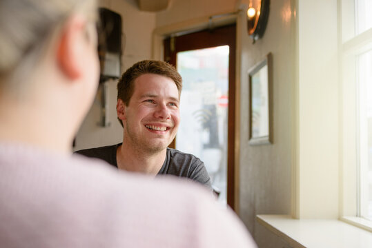 Happy man with girlfriend resting in cafe
