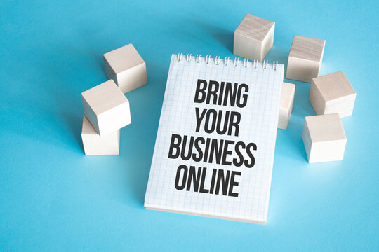 Text BRING YOUR BUSINESS ONLINE on white notepad with cube block, stock concept.