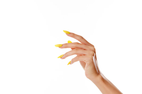 Closeup shot of a female's hand with yellow nail polish on a white background