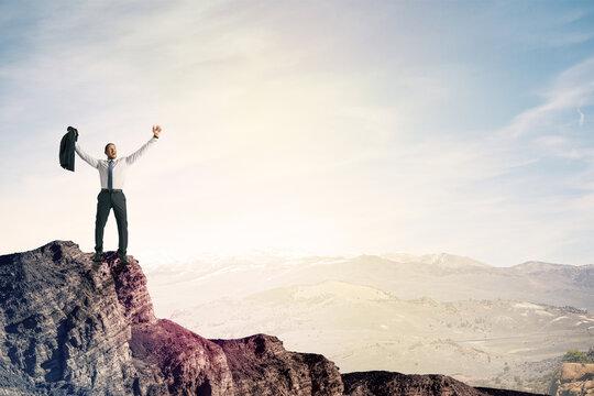 Happy businessman on cliff