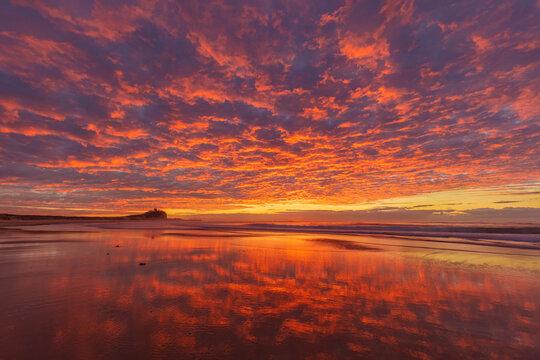 Stunning winters sunrise over Nobbys  Beach. Nobbys Lighthouse in the distance. Newcastle, Hunter Region of N.S.W. Australia.