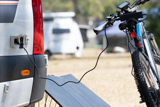 Electric  bicycle battery being charged from RV campervan using solar energy and inverter system