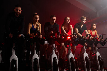youth biking in spinning class at modern gym, exercising on stationary bike. strong male and female training on exercise bike