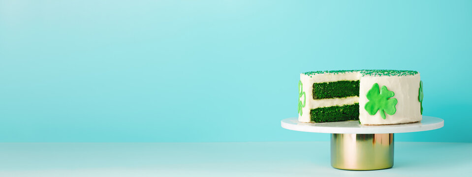St Patricks Day sweet food concept. Green velvet cake decorated green shamrock leaves for Saint Patrick's Day party on blue background. Copy space. Long horizontal banner