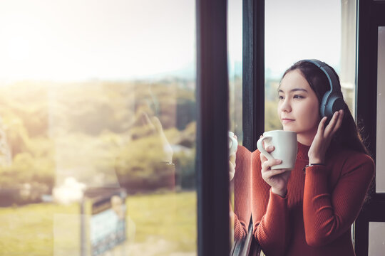 Beautiful woman on a casual day in asia listen to music with headphones. Sip coffee and look out the window at the coffee shop.