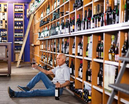 Portrait of cheerful senior man sitting on floor in winery tasting room, drinking red wine