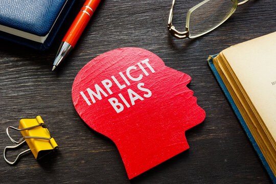 Implicit bias word on the head shape on the desk.