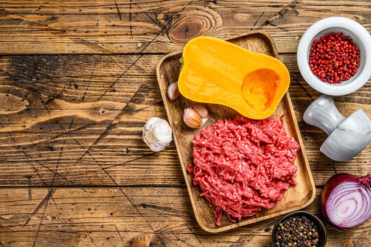 Cooking pumpkin with mince meat, garlic and onion. Wooden background. Top view. Copy space