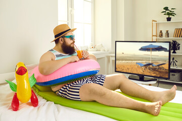 Funny young man with sunglasses and inflatable beach toys sipping cocktail and watching travel show...