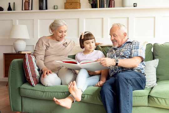 Loving 60s grandparents reading book with little granddaughter on sofa in living room. Caring grandfather and grandmother help learning to cute little girl together. Concept of education