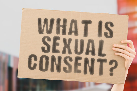 """The question """" What is sexual consent? """" on a banner in men's hand with blurred background. Intimacy. Intimate. Sex. Adult. Law. Relationship. Love. Legality"""
