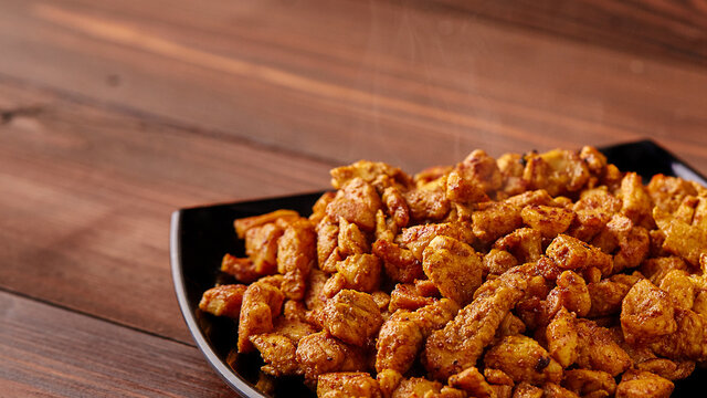 finely chopped chicken fillet fried in curry spices for salad preparation, ingredients on a plate on a wooden background