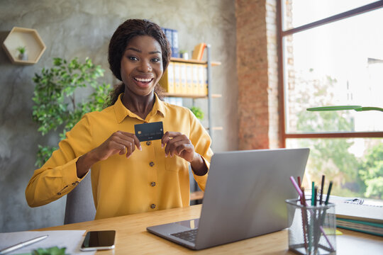 Photo of charming afro american woman hold credit card sit office table laptop happy salary indoors in workplace