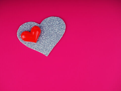 Valentine's Day concept, silver and red heart on pink background, greeting card