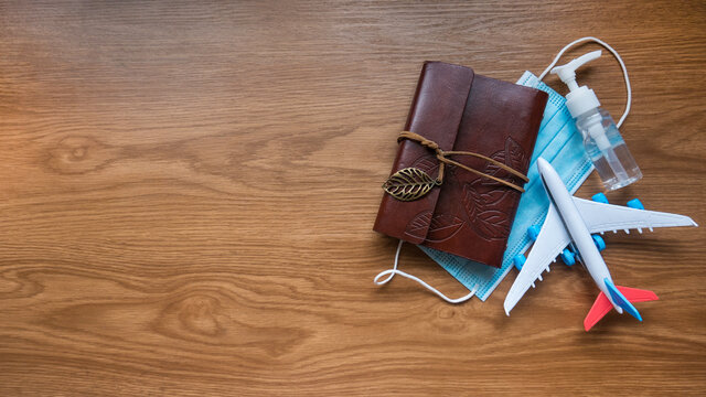 Top view of notebook,toy plane,hand sanitizer and face mask on a wooden background with copy space.Covid-19 and travel concept.
