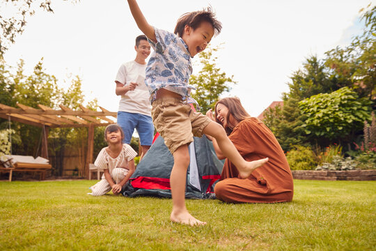 Asian Family In Garden At Home Putting Up Tent For Camping Trip Together