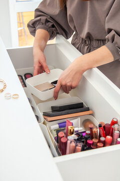 Woman hands neatly organising makeup and cosmetics in the drawer of vanity dressing table