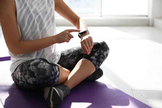 Woman checking fitness tracker in gym, closeup