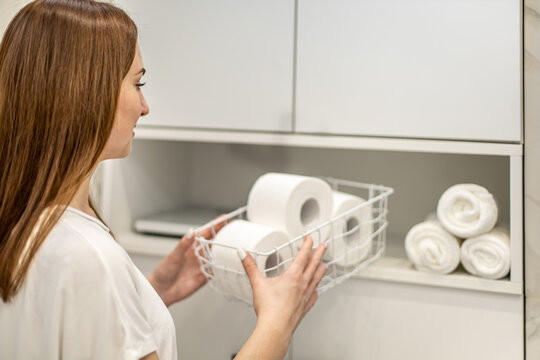 Young woman is organizing and placing metal mesh with toilet paper rolls in bathroom cupboard.