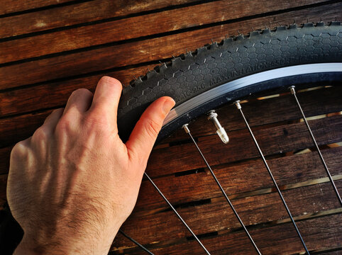 A hand manipulating a bicycle tire for mending, maintenace and repair of mountain bike tube. Wooden workbench in background.