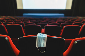 A medical mask hangs on a chair in an empty cinema hall. Pandemic and crisis in the industry....