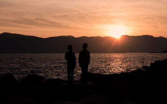 tramonto lago mare siluette bambini paesaggio panorama yoga benessere