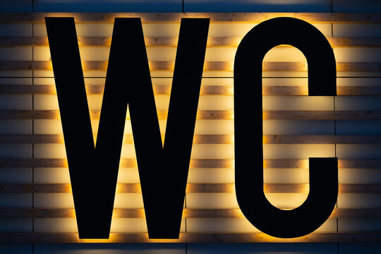 Yellow backlit black WC sign on wooden strips wall