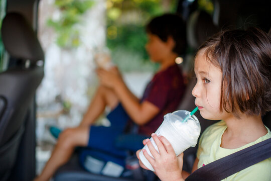 Two children sit in open car in summer sipping on cold drinks