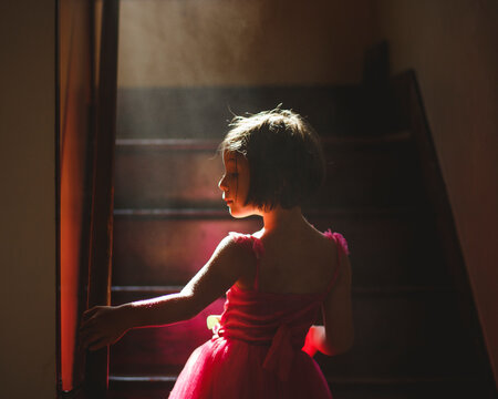 A graceful child stands in hazy light on dark staircase in fancy dress