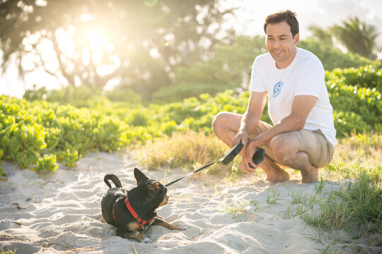 Young fit male squats on the beach with his small black dog in Hawaii