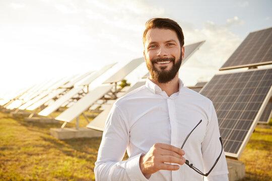 Cheerful male investor on solar farm