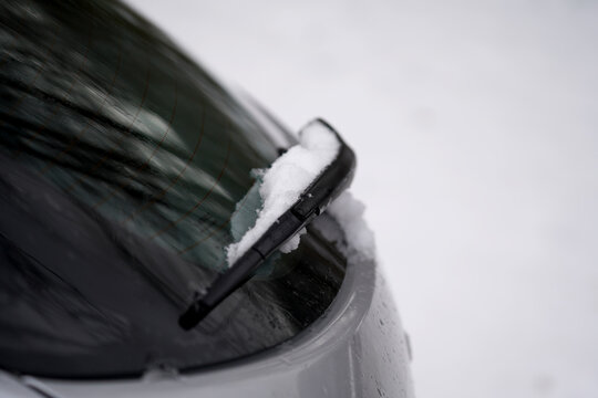 Closeup shot of a car wiper with some snow on white background