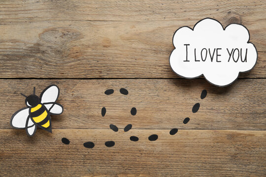 Card design with paper bee and phrase I Love You. Composition on wooden background, flat lay