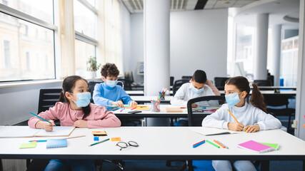 Diverse pupils wearing face masks keeping social distance