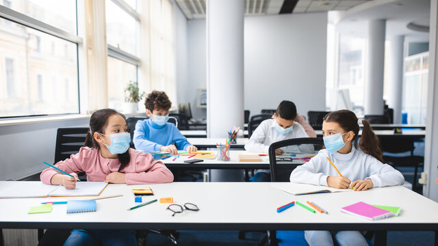 Diverse pupils wearing face masks keeping social distance