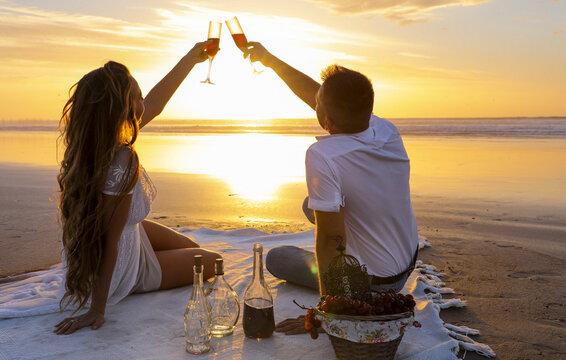 A gentle romantic date on the ocean during the magical sunset. A girl and a guy in white clothes sit on a white bedspread on the ocean during a magical sunset and drink a drink from beautiful glasses.