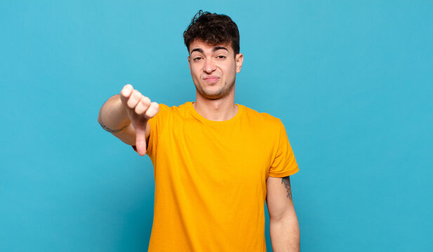 young man feeling cross, angry, annoyed, disappointed or displeased, showing thumbs down with a serious look