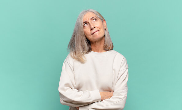 middle age woman doubting or thinking, biting lip and feeling insecure and nervous, looking to copy space on the side