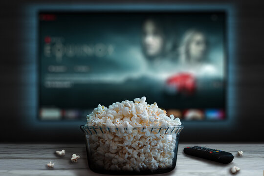 Video streaming app on tv screen behind a bowl of popcorn and a remote control.