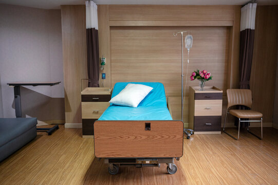 Empty adjustable patient bed with saline solution in private room at hospital